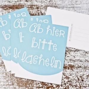 Postkarte Ab hier bitte lächeln